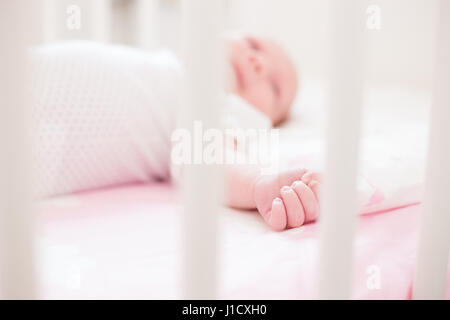 Detail shot of baby's hand on pink sheets with cloud pattern. Shallow depth of field, natural light. - Stock Photo