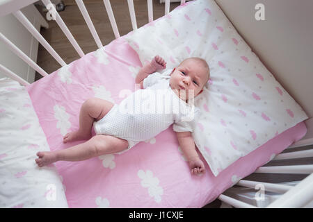 Two week old baby girl sleeping in her crib on pink sheets with cloud pattern. - Stock Photo