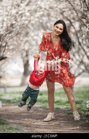Young mother with her baby on walk in blooming garden. They play and laugh cheerfully among flowering apricot trees. - Stock Photo