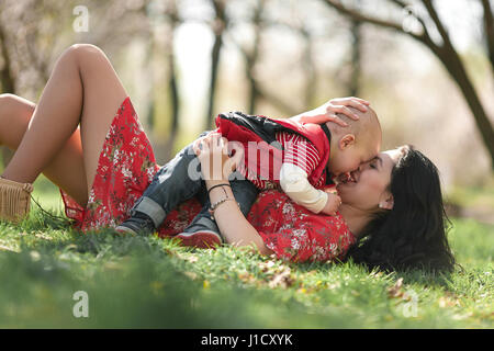 Young mother playing with  her baby on walk in spring garden. They lie on grass and having fun laughing. - Stock Photo
