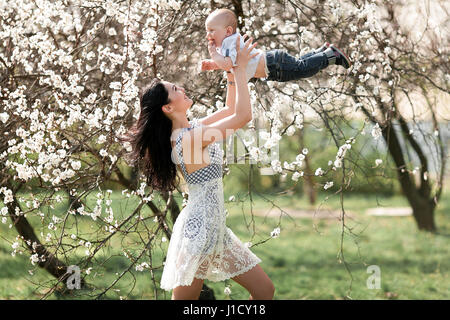 Young mother playing with  her baby on walk in blooming garden. She tosses up baby and they laugh joyful. - Stock Photo