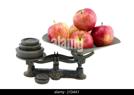 An antique kitchen scales with five apples held in it's tray ready for weighing. Isolated on a white background. - Stock Photo