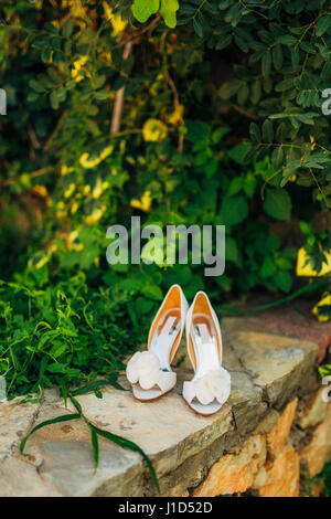 Wedding shoes on a stone border against a background of green leaves - Stock Photo