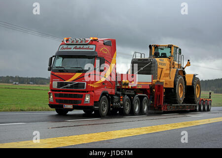 FORSSA, FINLAND - SEPTEMBER 4, 2016: Red Volvo FH12 semi truck transports Volvo wheel loader as oversize load parked - Stock Photo