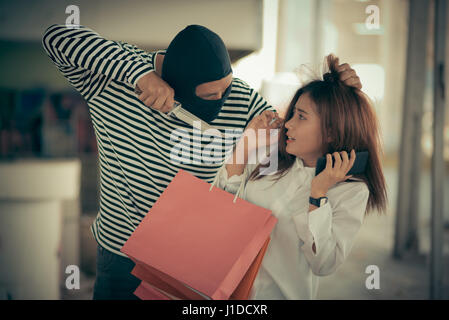 Street thief stealing young woman shopping bag and threatening with knife, Vintage tone style - Stock Photo