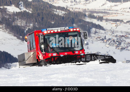 FLACHAU, AUSTRIA - DEC 27, 2012: Snow groomer on the ski piste in the ski resort town of Flachau. These pistes are - Stock Photo
