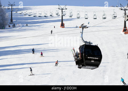 FLACHAU, AUSTRIA - DEC 29, 2012: Ski lift cable booth going up the piste in the Austrian Alps. These pistes are - Stock Photo