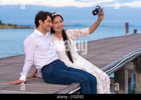 Smiling young couple making selfie while sitting on wooden bridge near the sea - Stock Photo