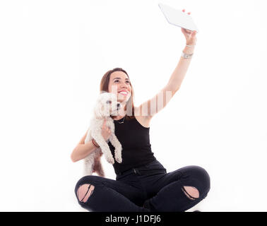 pretty girl takes a selfie with his dog on white background - Stock Photo