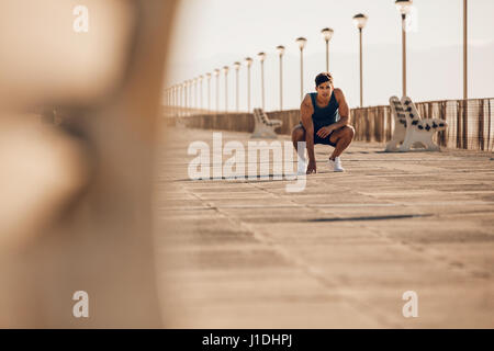 Shot of healthy young man taking a break after morning run. Male runner resting after running on promenade. - Stock Photo