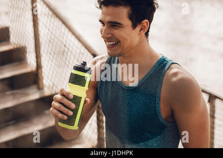 Athlete resting after running with bottle of water. Rest after a hard workout at beach. - Stock Photo
