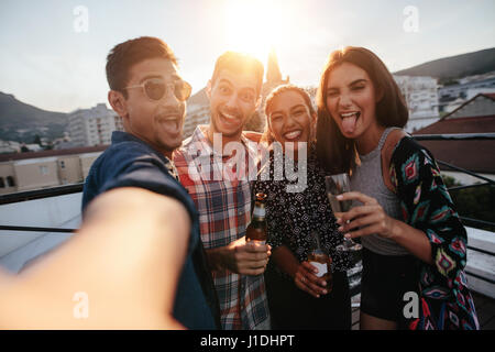 Group of people having a party on the rooftop making a selfie. Happy young friends taking self portrait during party. - Stock Photo