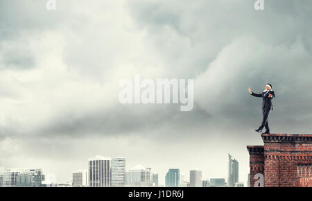 Danger and risk concept with businessman making step from edge - Stock Photo