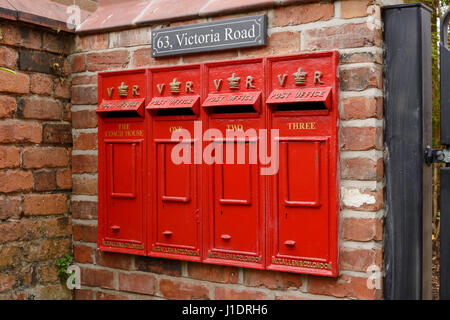 A row of four vintage reproduction mail boxes outside a multi occupancy property. - Stock Photo