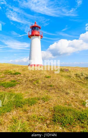 Lighthouse on sand dune against blue sky with white clouds on northern coast of Sylt island near List village, Germany - Stock Photo