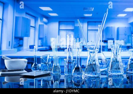 Modern laboratory  equipment , set of different glassware on blue background. - Stock Photo