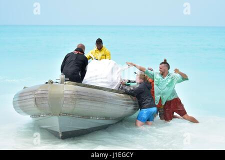 Hawaiian State employees lift a bag of trash into a boat as they collect plastic and marine debris washed ashore - Stock Photo