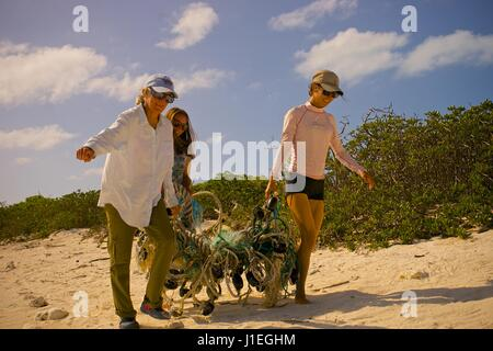 Hawaiian State employees carry piles of trash as they collect plastic and marine debris washed ashore on Kure Atoll - Stock Photo