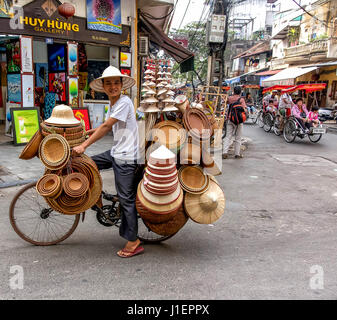 A street vendor on his bicycle selling hats in Hanoi, Vietnam. - Stock Photo