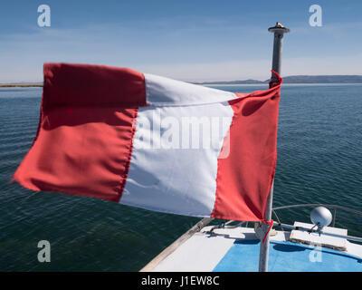 Sailing under the Peruvian flag on Lake Titicaca, Puno Region, Peru - Stock Photo