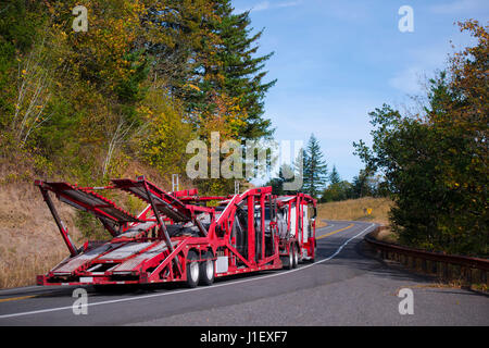 Big rig Semi Truck Car Hauler with red specialized trailer for transportation several cars moving on a winding crooked - Stock Photo