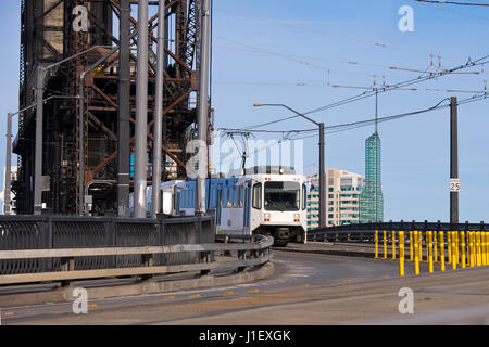 Modern white streetcar and power lines on the turn from the old drawbridge with rusty farm across the river Willamette - Stock Photo