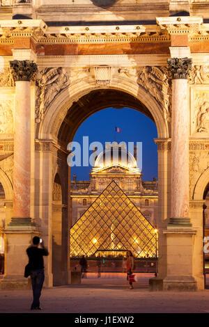 Tourists taking photos at Arc de Triomphe du Carrousel with Musee du Louvre beyond, Paris France - Stock Photo