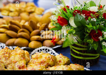 Small pies lie on a plate with basket of flowers on a blue table - Stock Photo