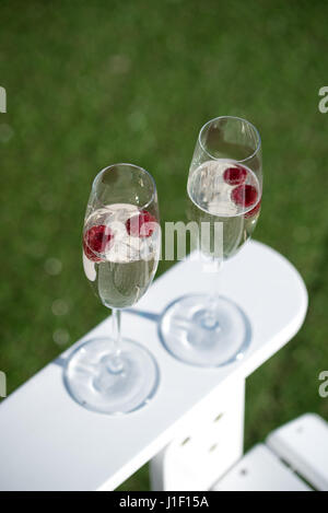 Two glasses of prosecco with raspberries on white garden chair with green grass. - Stock Photo