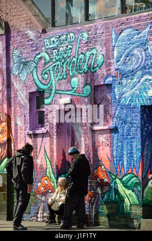 People standing in front of a mural painting on a brick wall. - Stock Photo