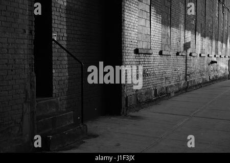 Old backstreet alley in DUMBO Brooklyn, New York at sunset Monochrome, black and white. - Stock Photo