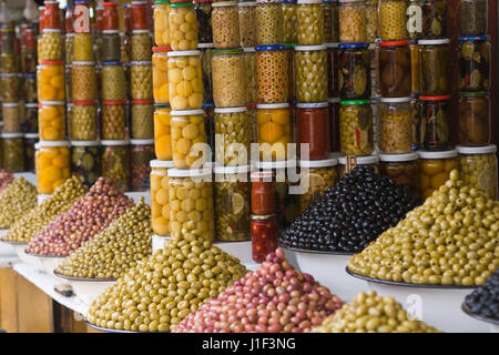 Market stall selling fresh olives and bottled food in the main souk of Marrakesh, Morocco. - Stock Photo