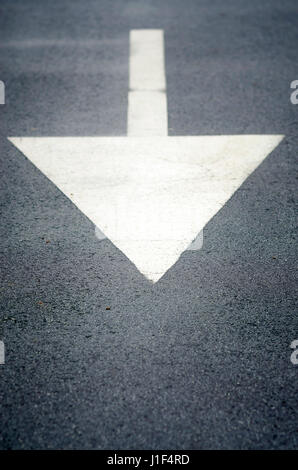 White painted direction arrow sign on asphalt road pointing backwards - Stock Photo