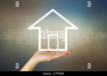 Home or property icon on hand on dark background. - Stock Photo