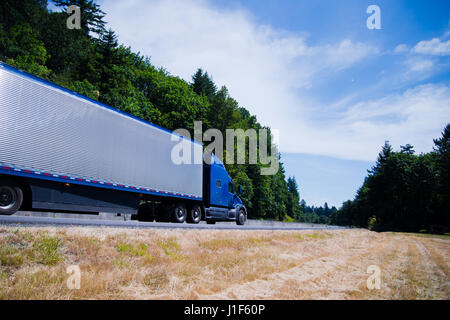 The modern model of the blue big rig semi truck with aluminum fluted corrugated refrigerator trailer speeding on - Stock Photo