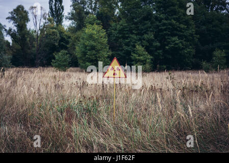 Ionising radiation warning sign in so called Red Forest area surrounding Chernobyl Nuclear Power Plant, Zone of - Stock Photo