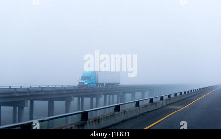 Modern big blue rig semi-truck with a trailer with lights on transports cargo on a long concrete viaduct over the - Stock Photo