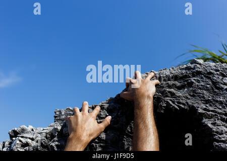 Man climbs on mountain slope - Stock Photo
