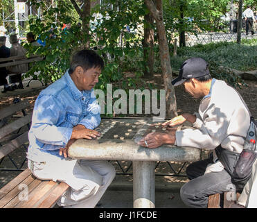 Men playing chinese chess in Columbus park in Chinatown, NYC - Stock Photo