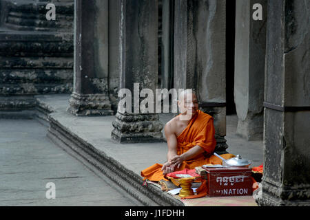 Buddhist monk sells prayers in the Angkor Wat temple complex in Siem Reap, Cambodia. - Stock Photo