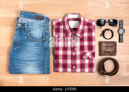 Men's casual outfits with accessories on wooden table, Red plaid shirt and blue jeans with eyeglasses, bracelet, - Stock Photo