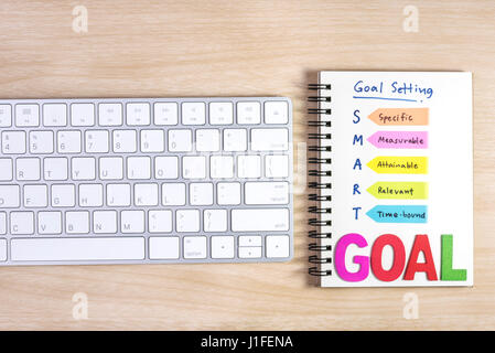 smart goals setting written on the notebook and keyboard over wooden table, business success concept - Stock Photo