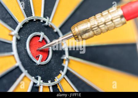closeup dart arrow hitting in target bullseye of dartboard, business data integration solutions and success concept - Stock Photo