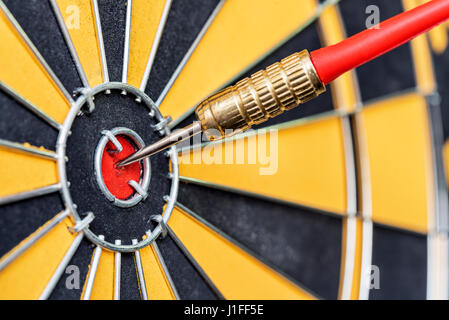 closeup red dart arrow hitting in target bullseye of dartboard, business solutions and success concept