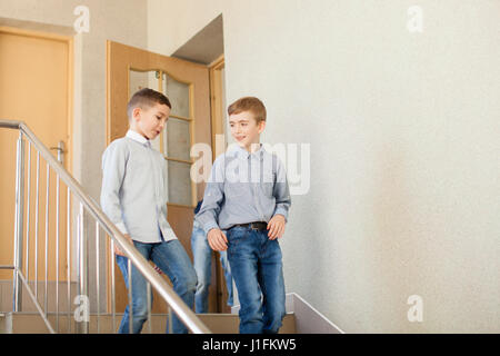 Two boys go downstairs  - Stock Photo