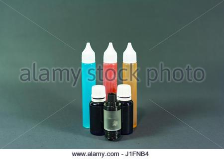 e cigarette liquid bottles on isolated black background photograph - Stock Photo
