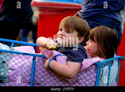 Two young children enjoying  sitting in a wagon  watching live music at Cornbury festival - Stock Photo