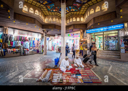 Muscat, Oman - Souq Muttrah Men sitting on carpet in market selling various traditional items - Stock Photo