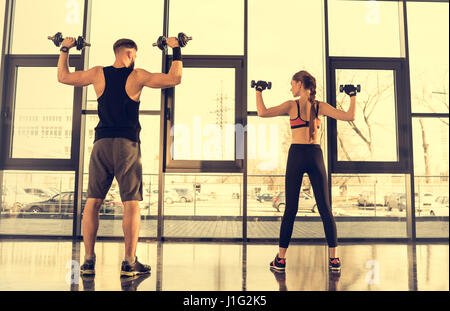 Back view of sporty man and woman exercising with dumbbells in gym - Stock Photo
