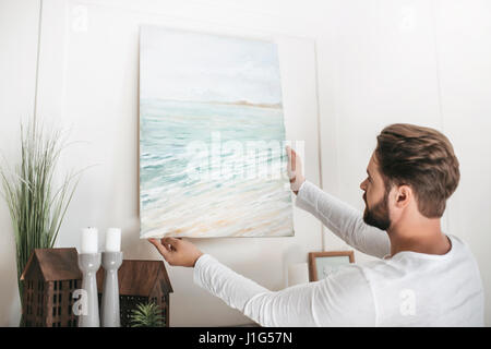 Young bearded man hanging picture on wall at home - Stock Photo